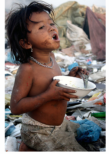 little boy eating garbage at the dump
