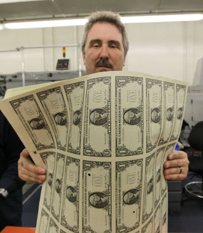 Man holding newly printed cash.